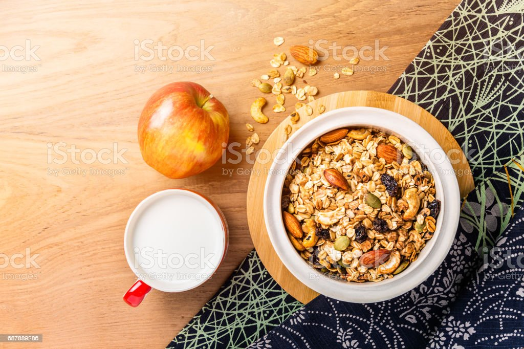 morning cereal in a bowl with full apple and cup of milk on wood table with asian style napkin, side warm morning light, room for copy space stock photo