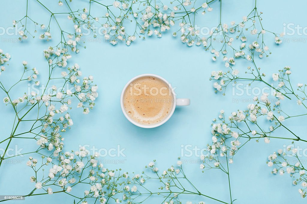 Morning cup of coffee and flower gypsophila on blue table from above....