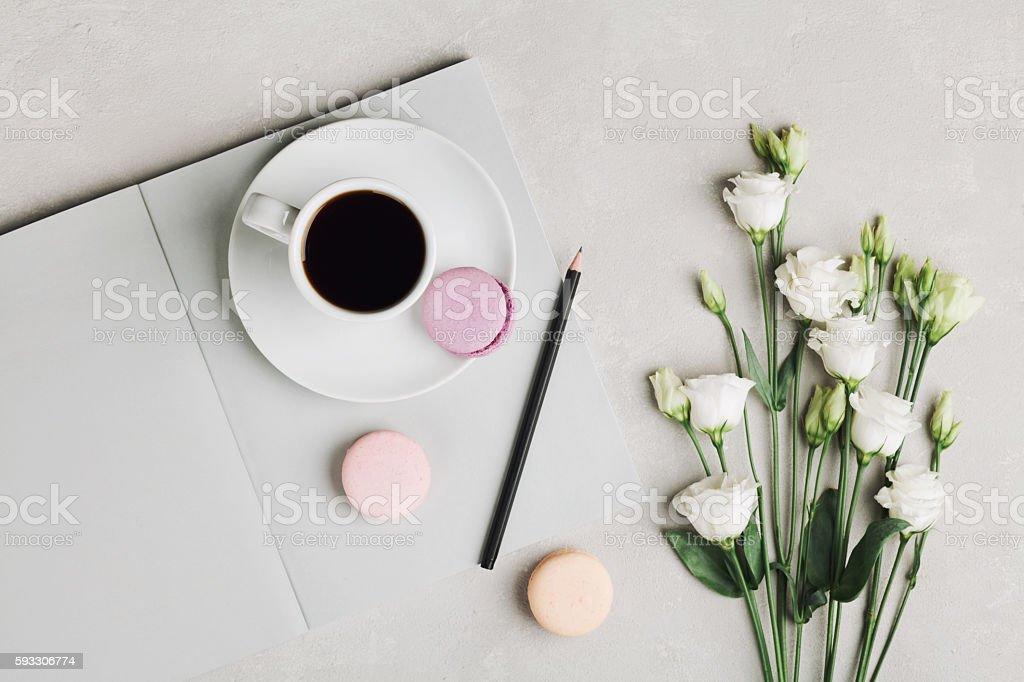 Morning coffee, empty notebook, flowers and cake macaron. Flat lay. stock photo