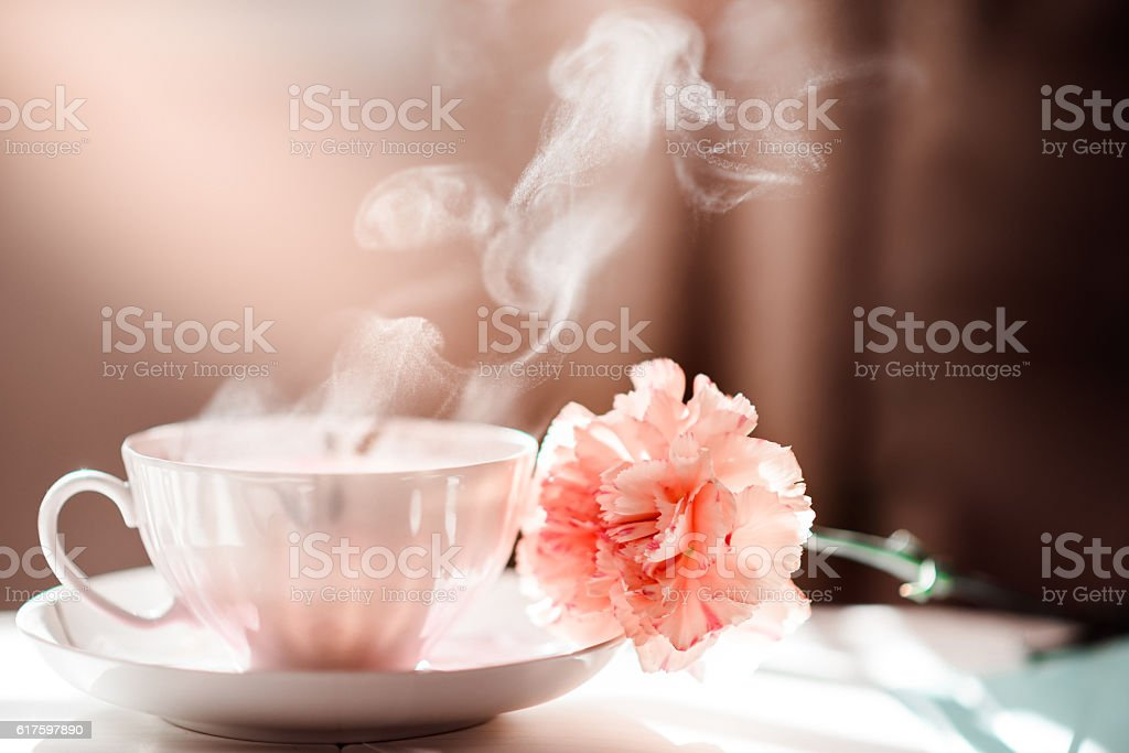 Morning Coffee Tea Cup with Steam and Carnation Flower stock photo