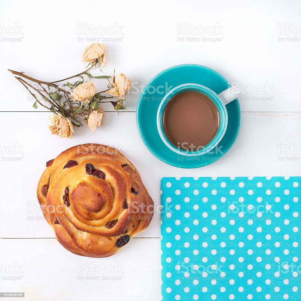Morning cup of coffee and a bun with raisins. stock photo