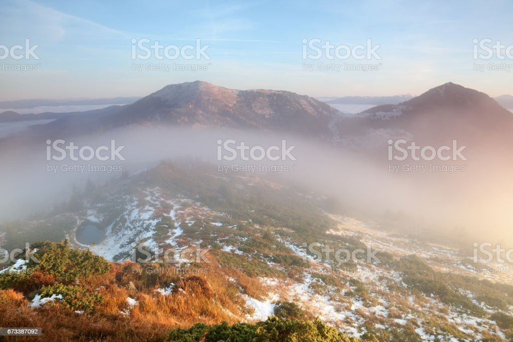 Morning fog covered the lawn with the lake high at the mountains in the sunny autumn day. stock photo