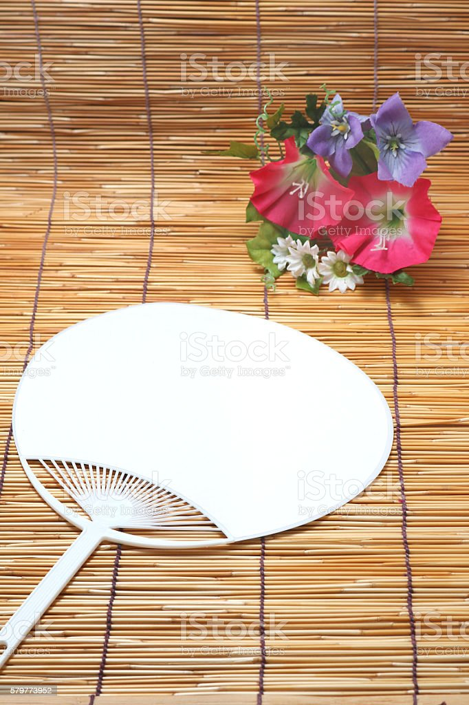 Morning glory and fan on bamboo blind. stock photo
