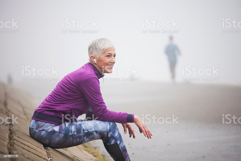 Beautiful mature woman jogging through fog in early autumn day