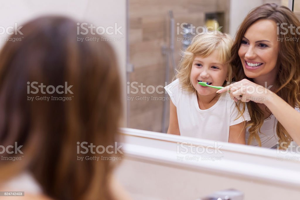 Morning lesson of brushing teeth with mommy stock photo
