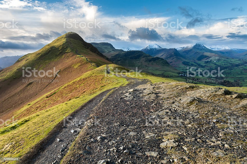Morning Light Shining On Catbells With Snow-Capped Mountains In Background stock photo