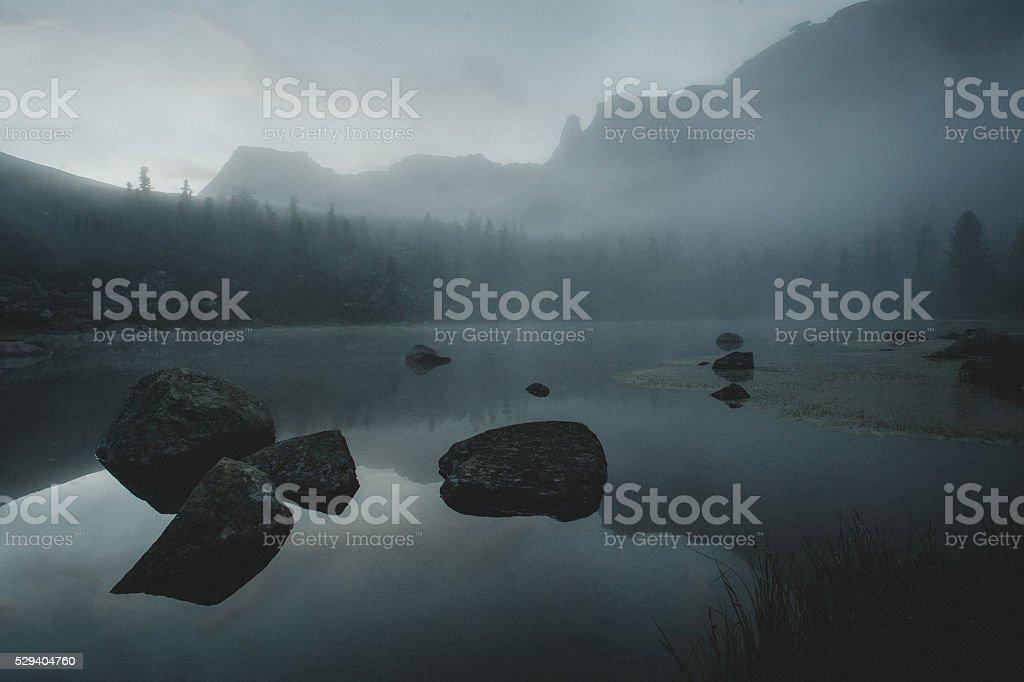 Morning mist lake. Mystical atmosphere before sunrise. Mountains background stock photo