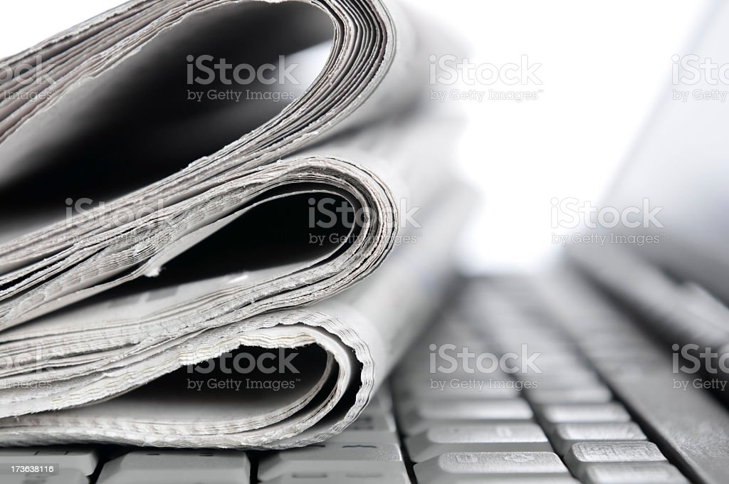 Morning news, folded newspapers lying on notebook keyboard, monochrome royalty-free stock photo