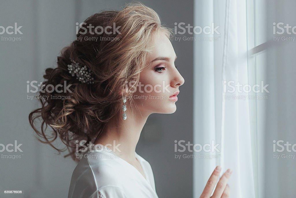 Morning of the bride. Beautiful young woman in elegant white stock photo