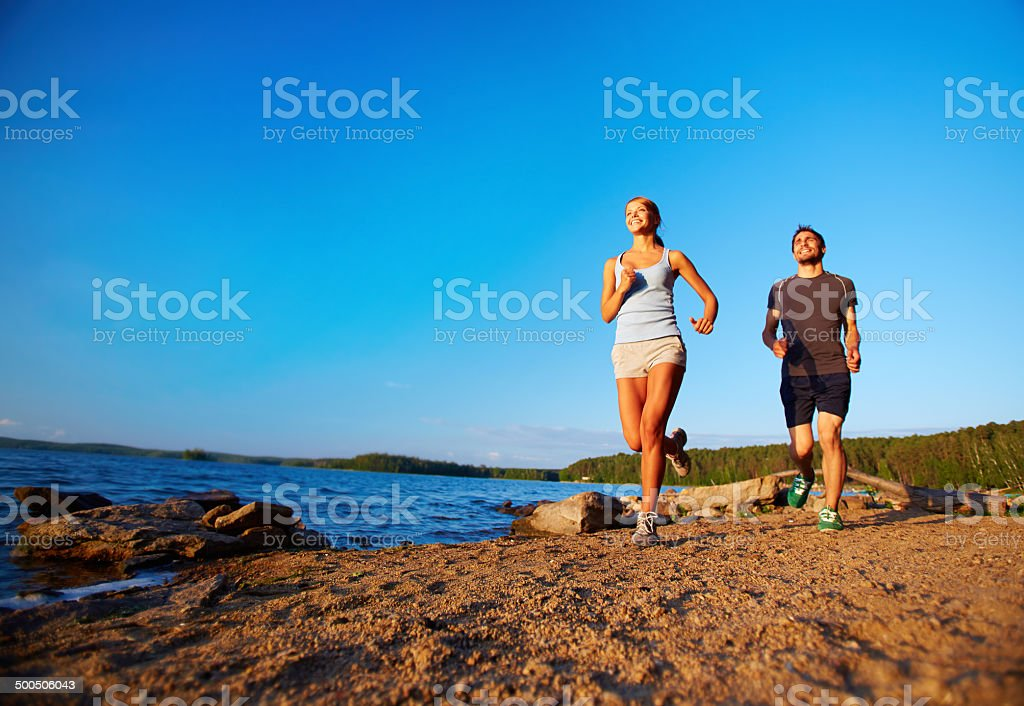 Photo of young couple running along coastline in the morning