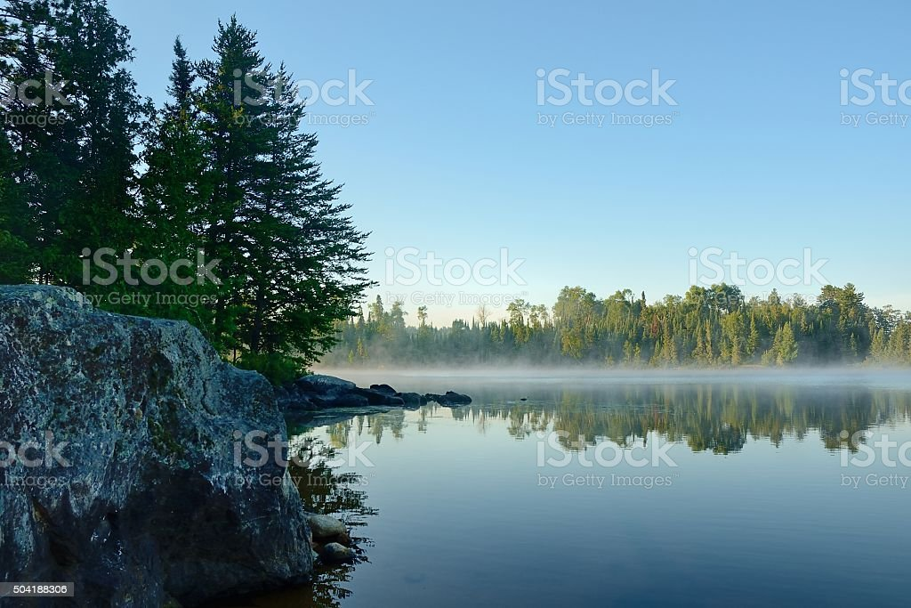 Morning Reflections on a Foggy Wilderness Lake stock photo