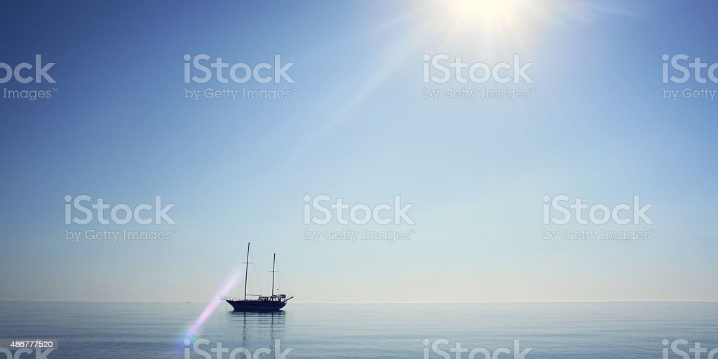 Morning sea with boat on the horizon. Aged photo. stock photo