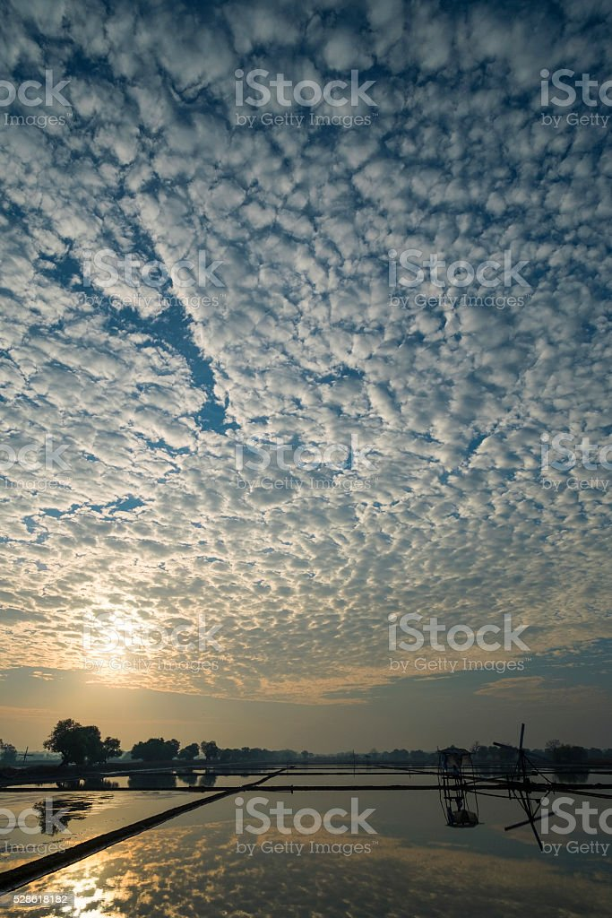 Morning sunrise with beautiful cloud formation in salt field stock photo