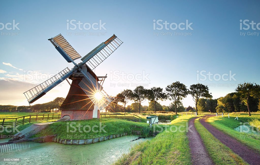 morning sunshine behind Dutch windmill stock photo