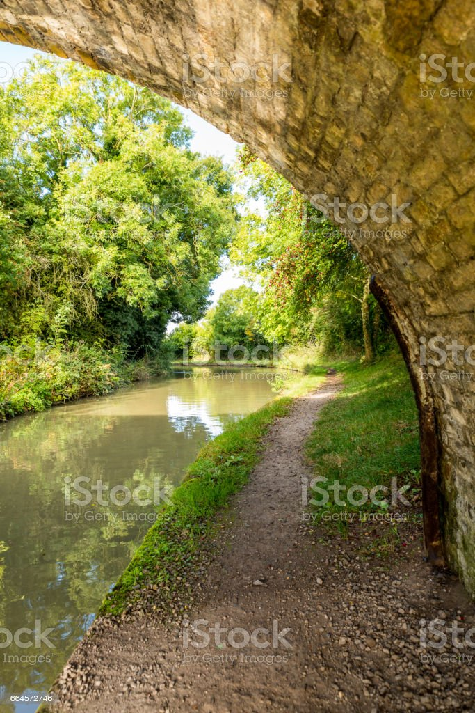 Morning view empty path under bridge along canal in England stock photo