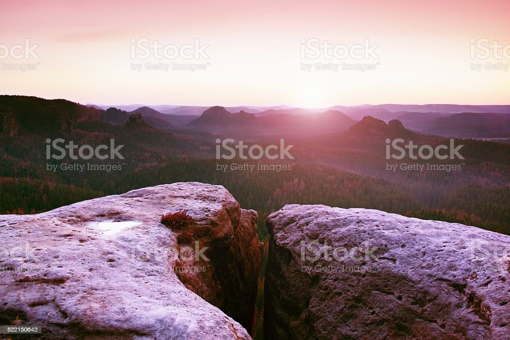 Morning view over cliff into forest valley, Sun at horizon. stock photo