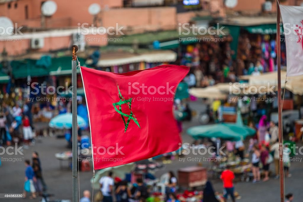 moroccan flag over djemaa el fna stock photo