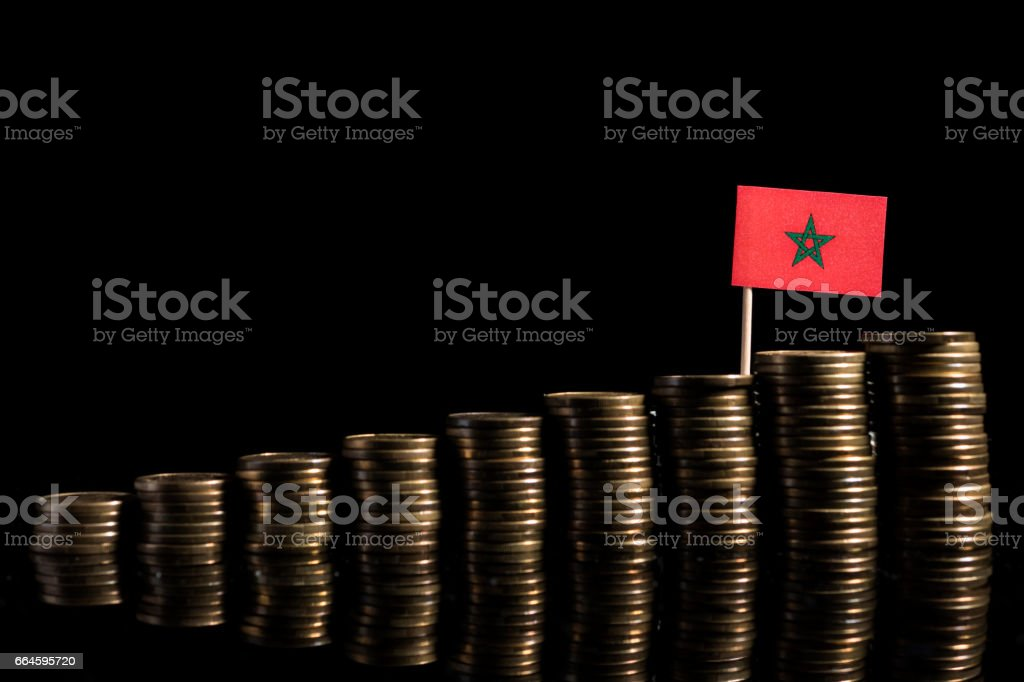 Moroccan flag with lot of coins isolated on black background stock photo