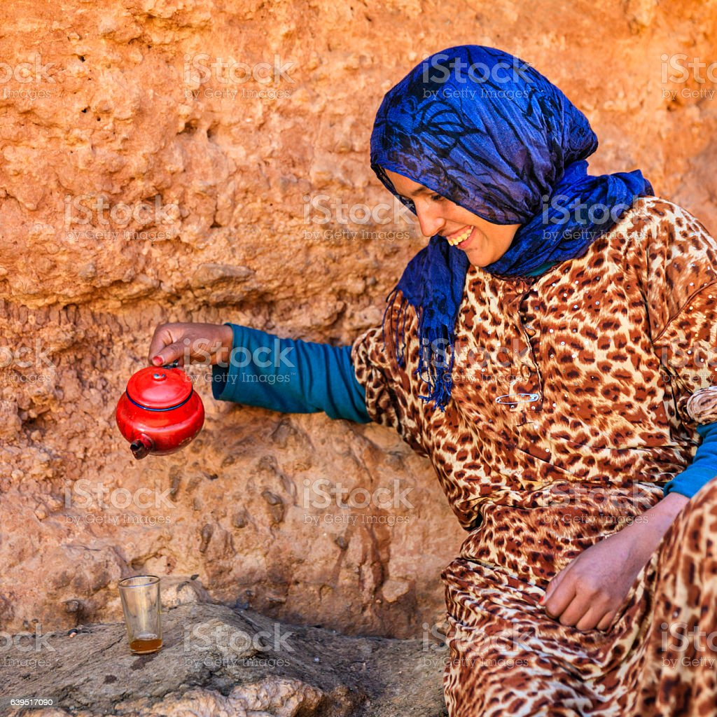 Moroccan girl preparing Maghrebi mint tea. stock photo