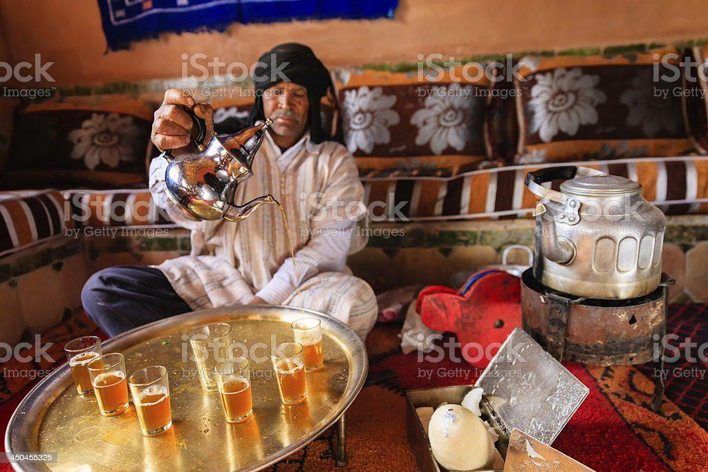 Moroccan man preparing Maghrebi mint tea. stock photo
