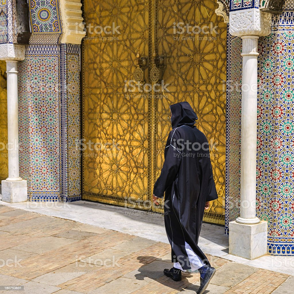 Moroccan man walking in front of The Royal Palace, Fes stock photo