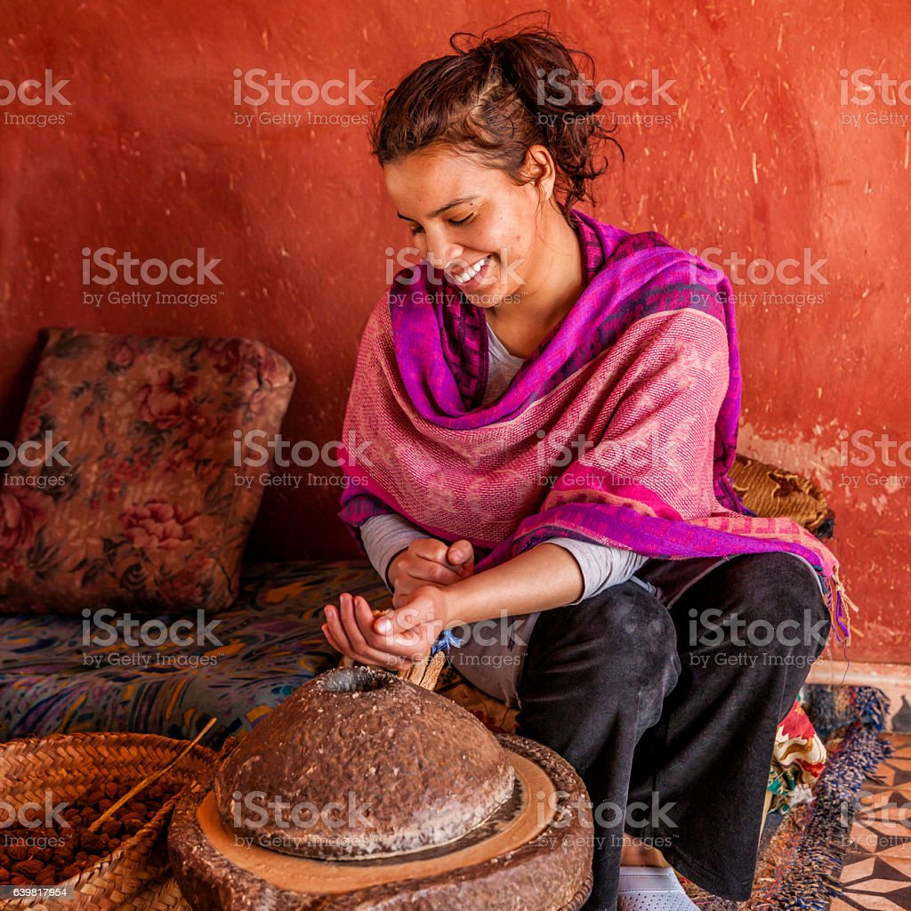Moroccan woman producing argan oil by traditional methods stock photo