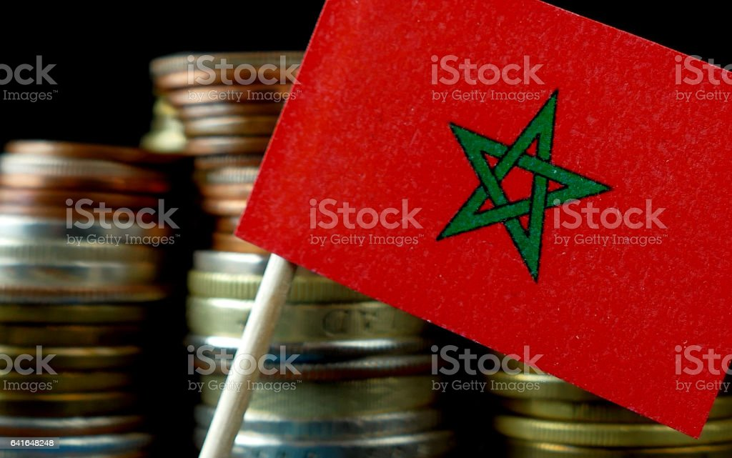 Morocco flag waving with stack of money coins macro stock photo