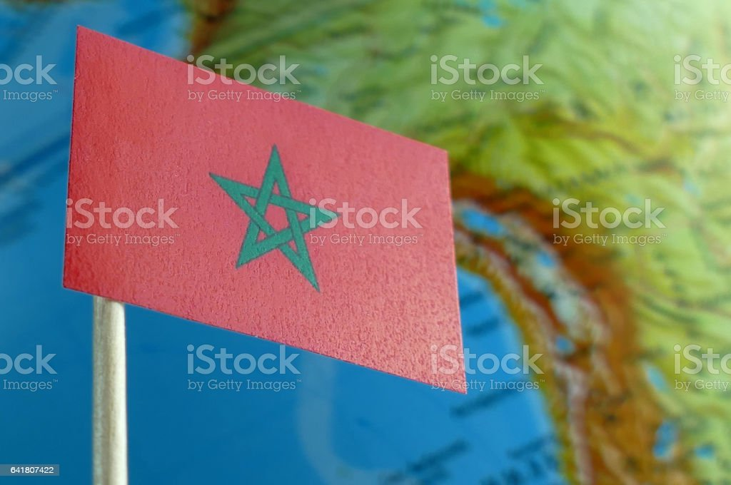 Morocco flag with a globe map as a background macro stock photo