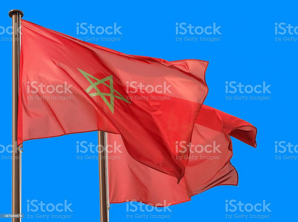 Morocco flags waving in blue sky stock photo