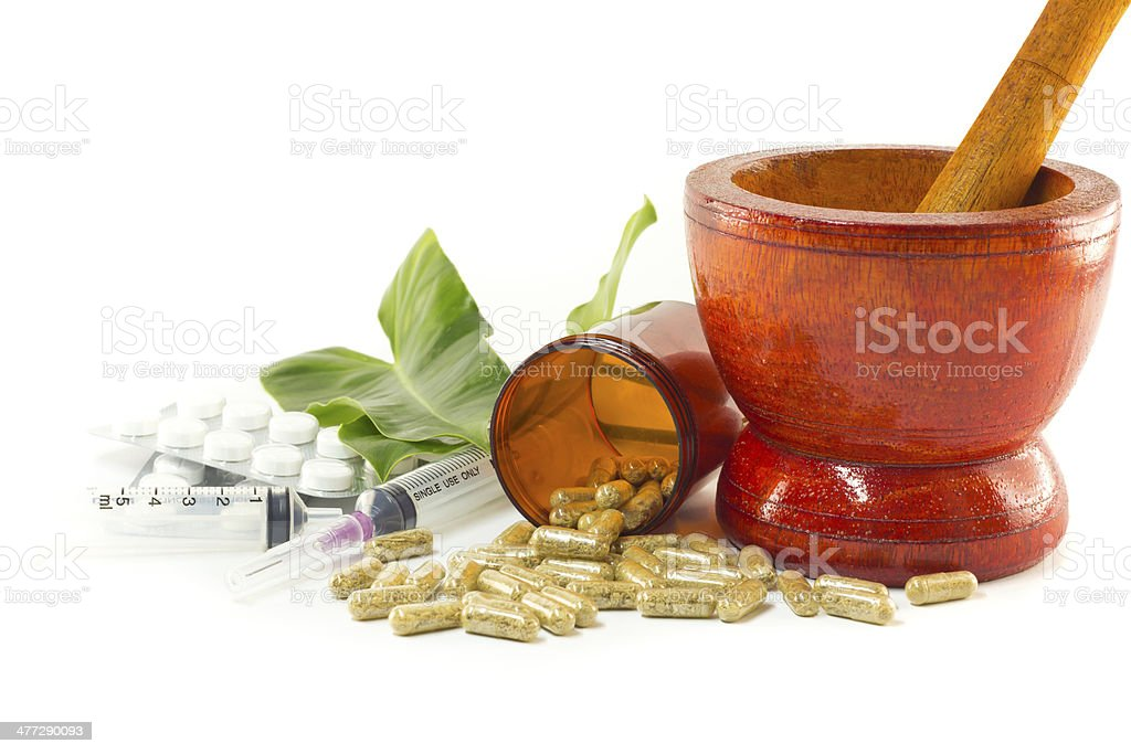 Mortar and pestle with herb capsules spilling out of bottle stock photo