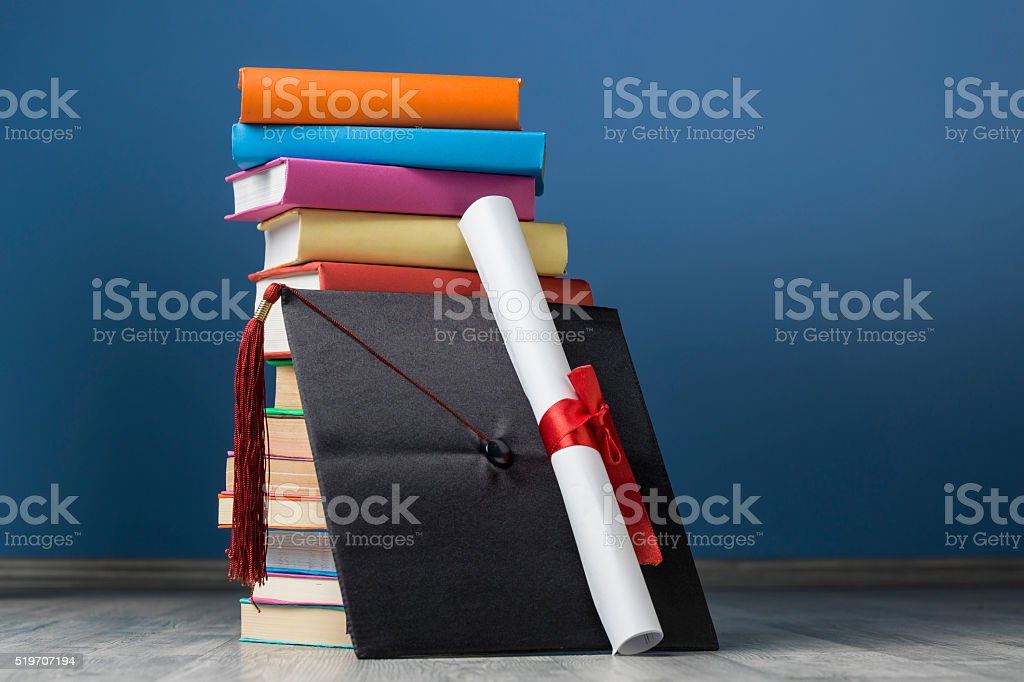 Mortar Board With Red Tassel Next To Multicolored Books stock photo