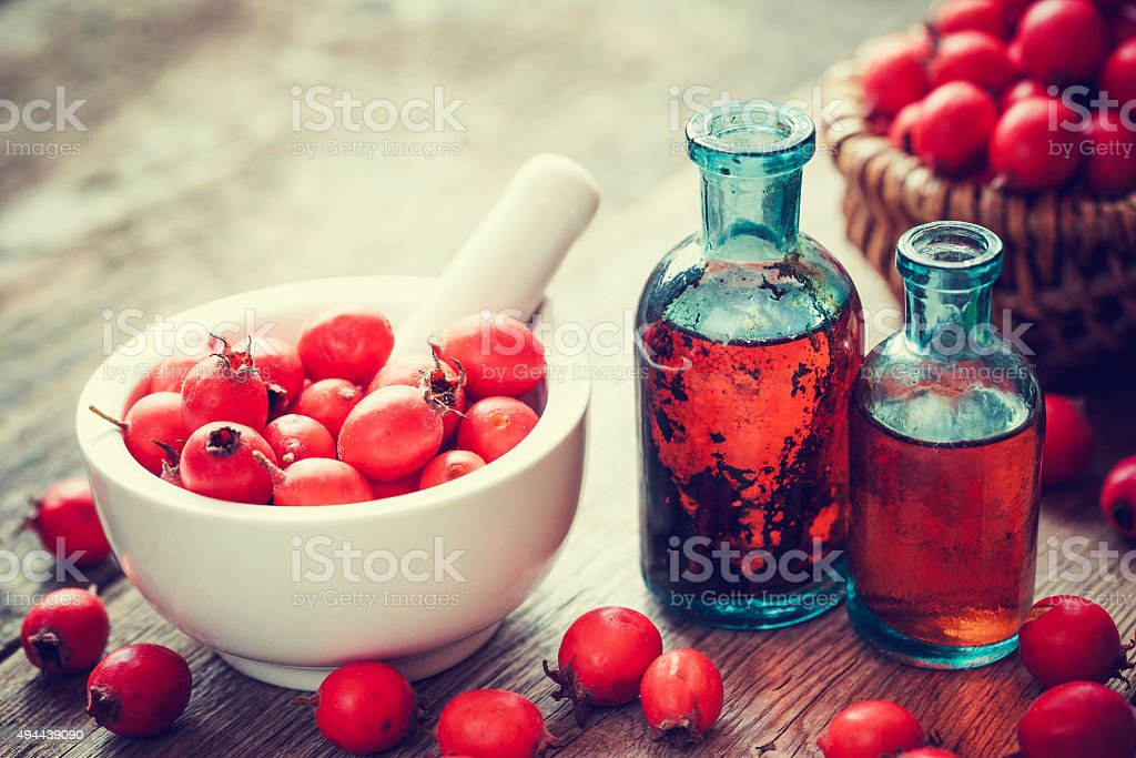 Mortar of hawthorn berries and tincture bottles stock photo