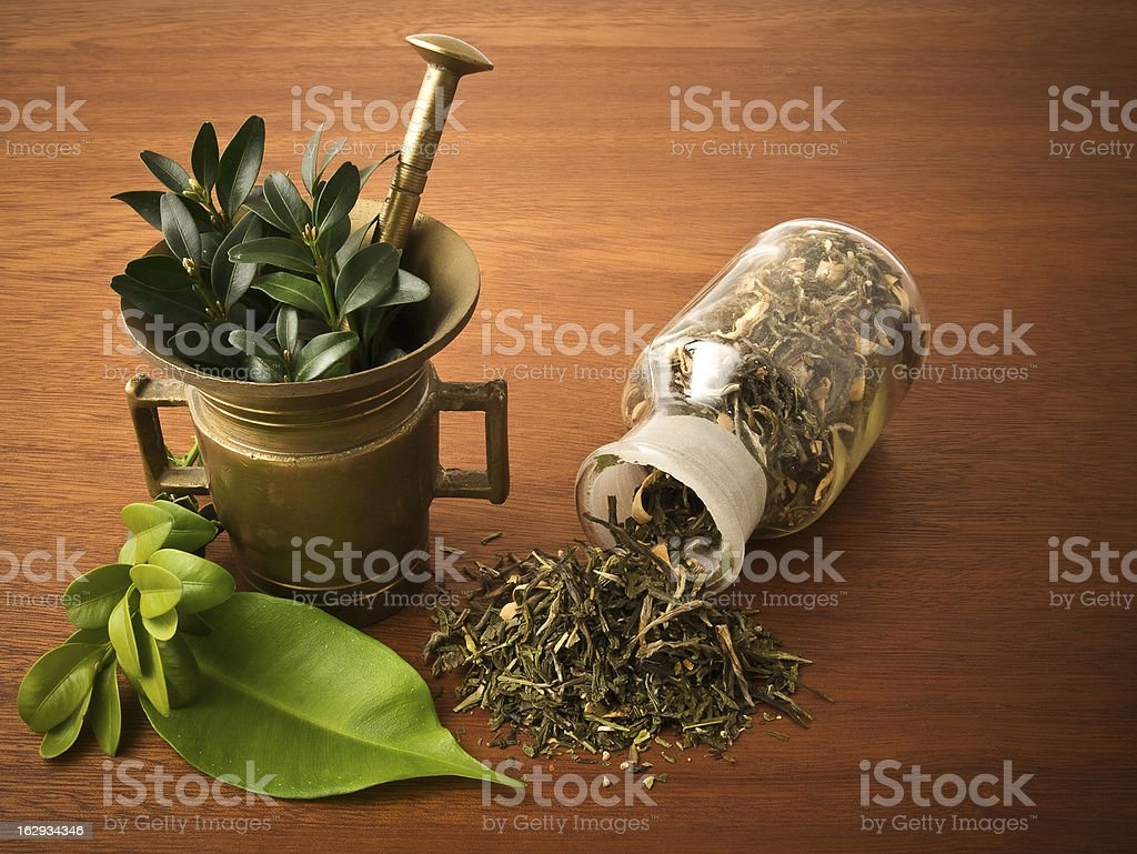 Mortar pestile and a prescription bottle full of herbs royalty-free stock photo