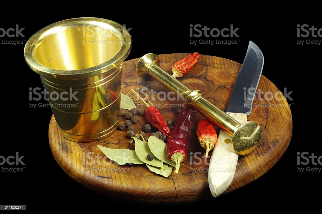 Mortar with pestle, knife and spices on the cutting board stock photo