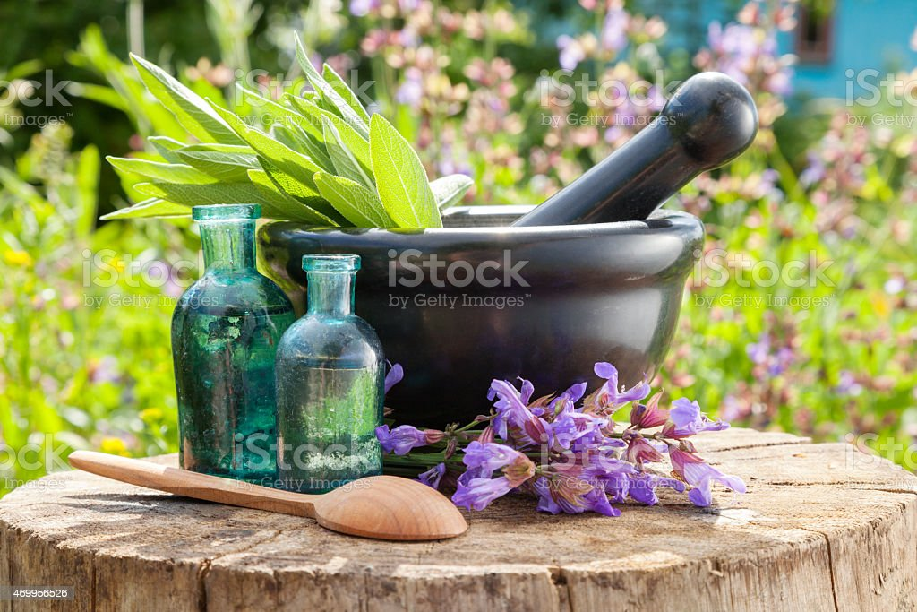 Mortar with sage herbs, glass bottles of essential oil stock photo