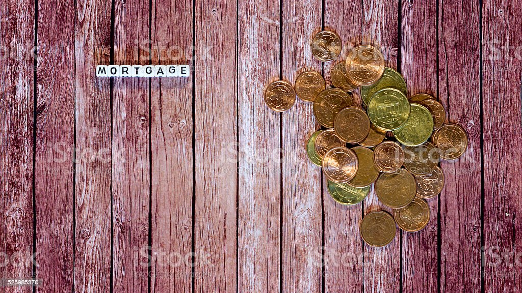 mortgage loan, letter cubes with coins on wooden material royalty-free stock photo