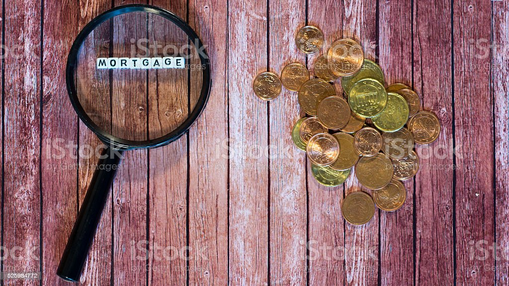 mortgage loan, magnifying glass and coins royalty-free stock photo