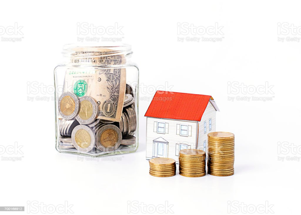 Mortgage loans concept with coins stack and paper house and saving bottle Isolated stock photo