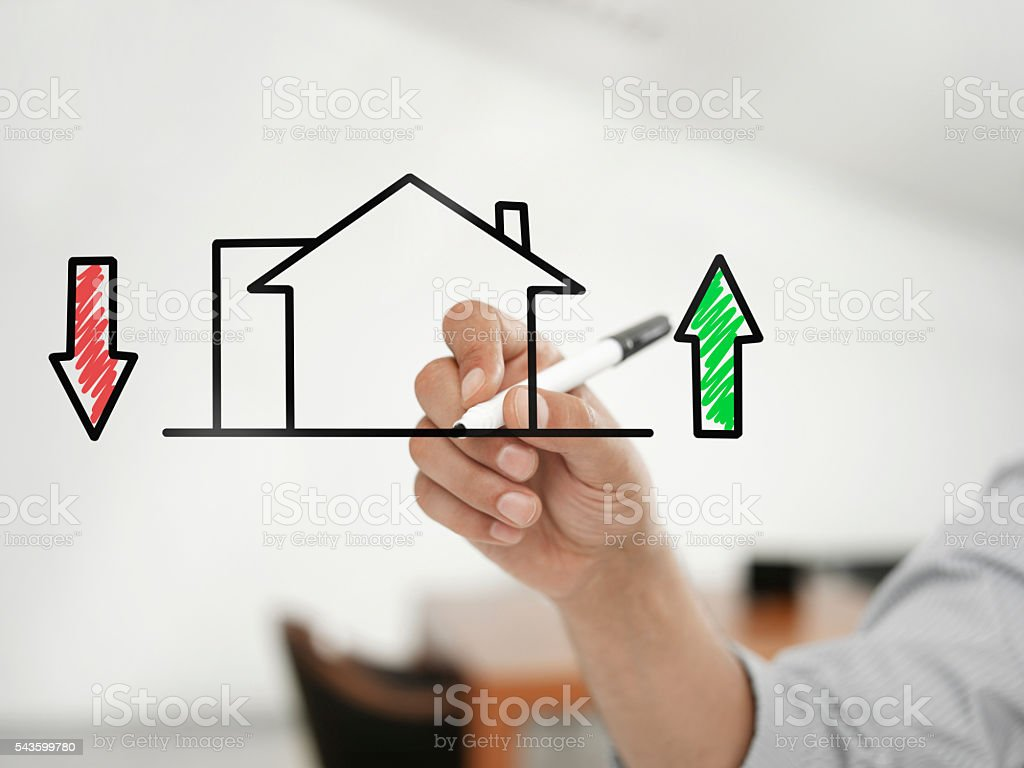 Businessman drawing \'house and mortgage rates\' on a virtual glass...