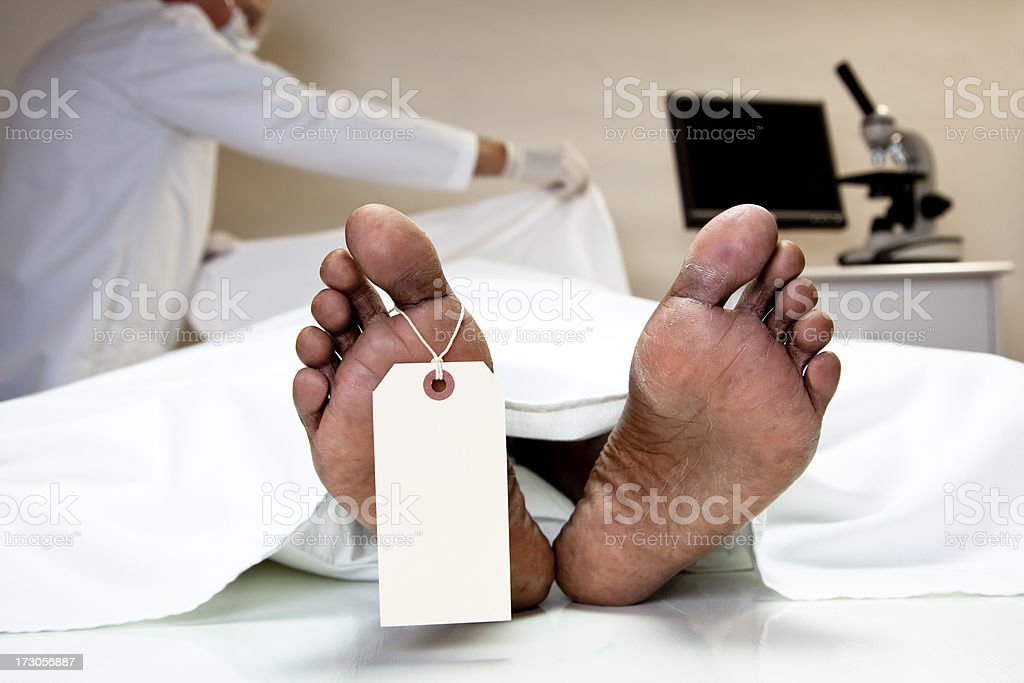 Mortician, coroner covering dead body in morgue. Feet, toe tag. stock photo