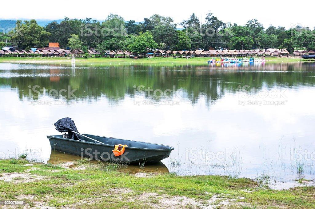 Mortorboat and orange life jacket beside lake with rafts stock photo