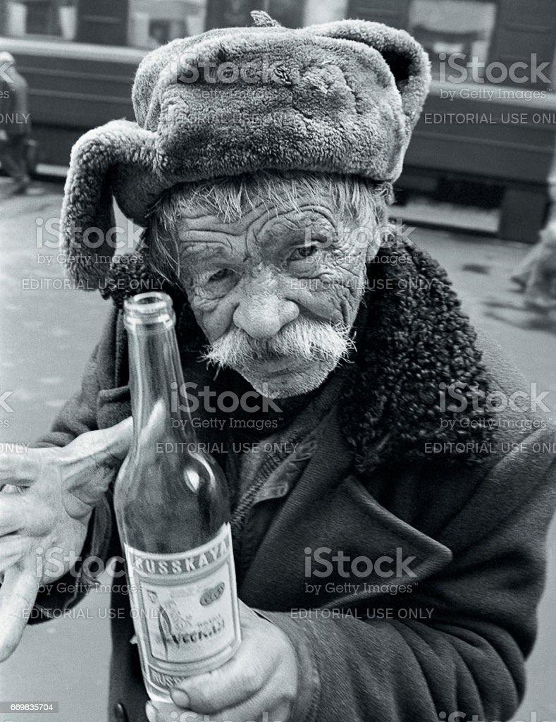 Moscow, Russia - March 27,2002: A drunk old man stands on the platform of the Moscow railway station and holds a bottle of vodka in his hands stock photo