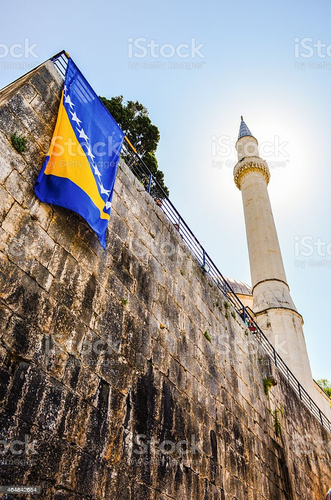 Mosque minaret with Bosnian flag in Pocitelj stock photo