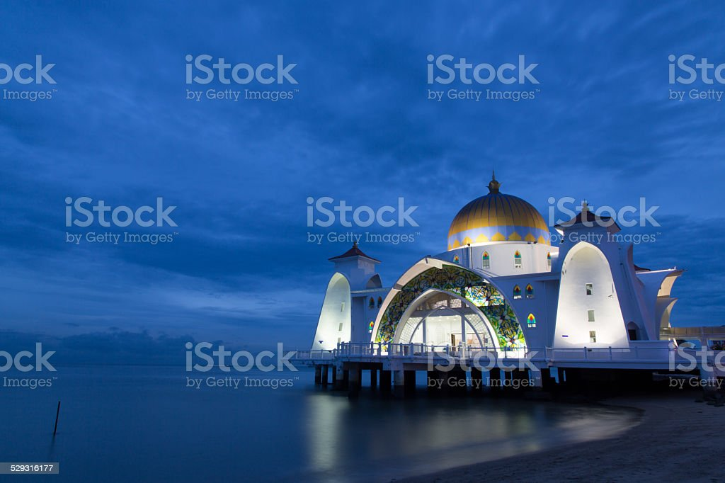 Mosque next to the sea during blue hour stock photo