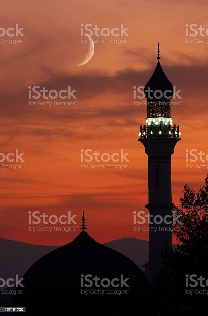 Mosque with crescent moon at dusk stock photo