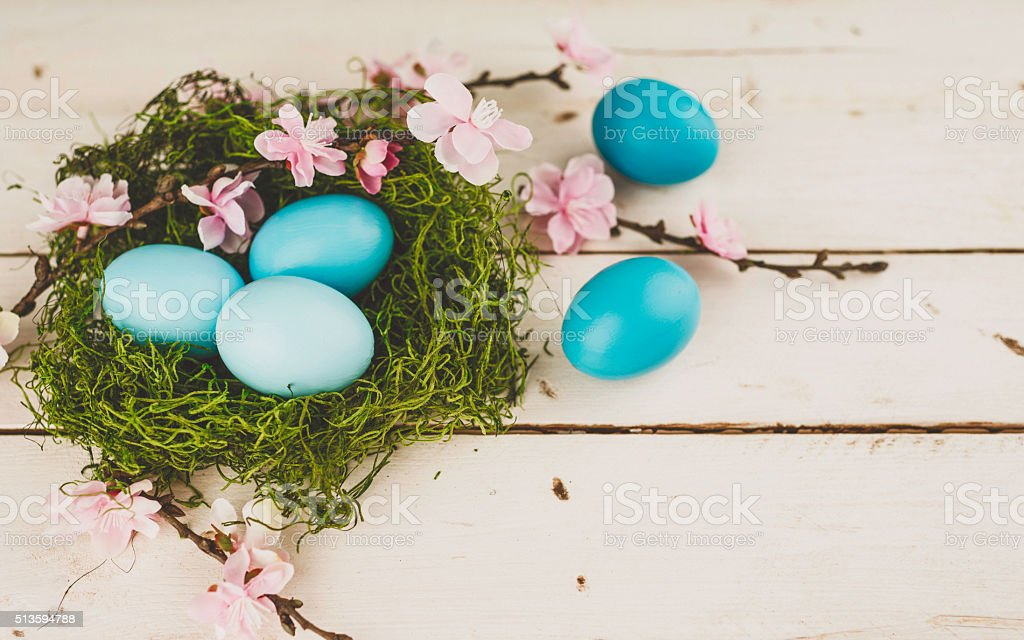 Moss nest with teal Easter eggs and blossoms. Easter arrangement. stock photo