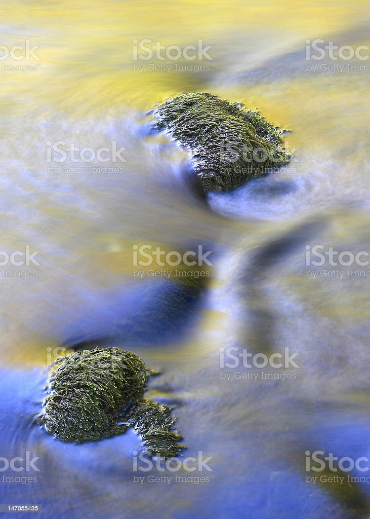 Mossy boulders in a colorful stream royalty-free stock photo