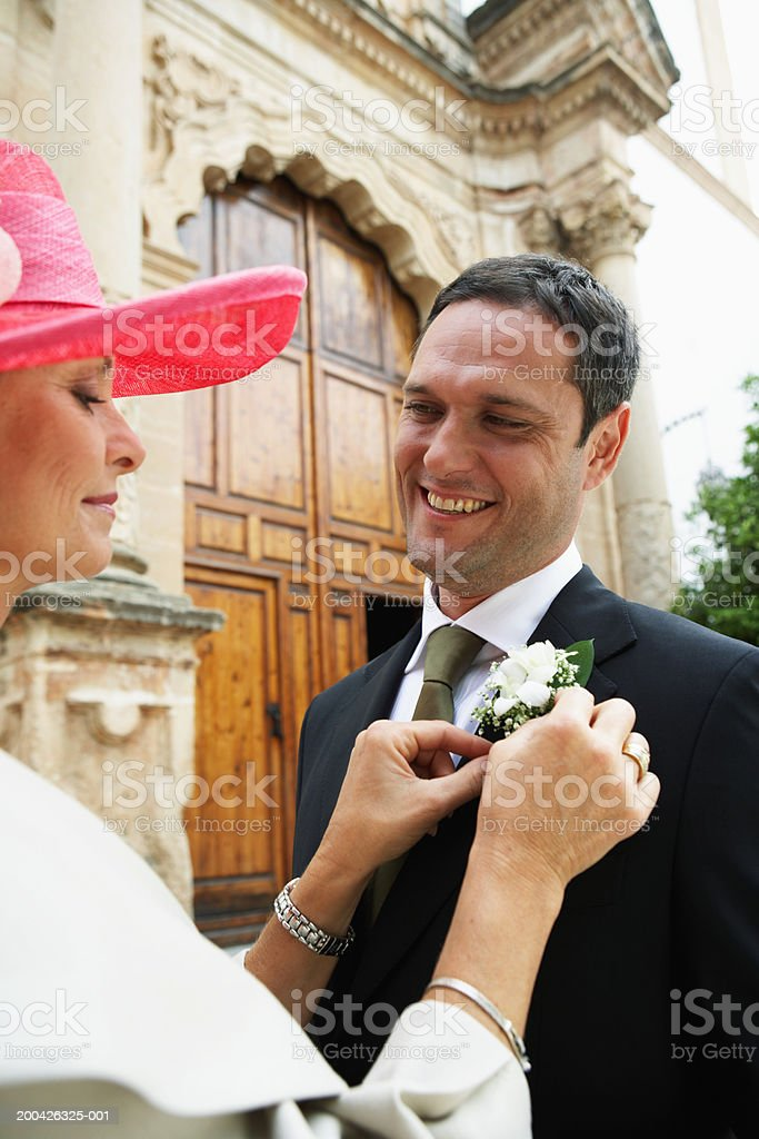 Mother adjusting groom's corsage outdoors royalty-free stock photo