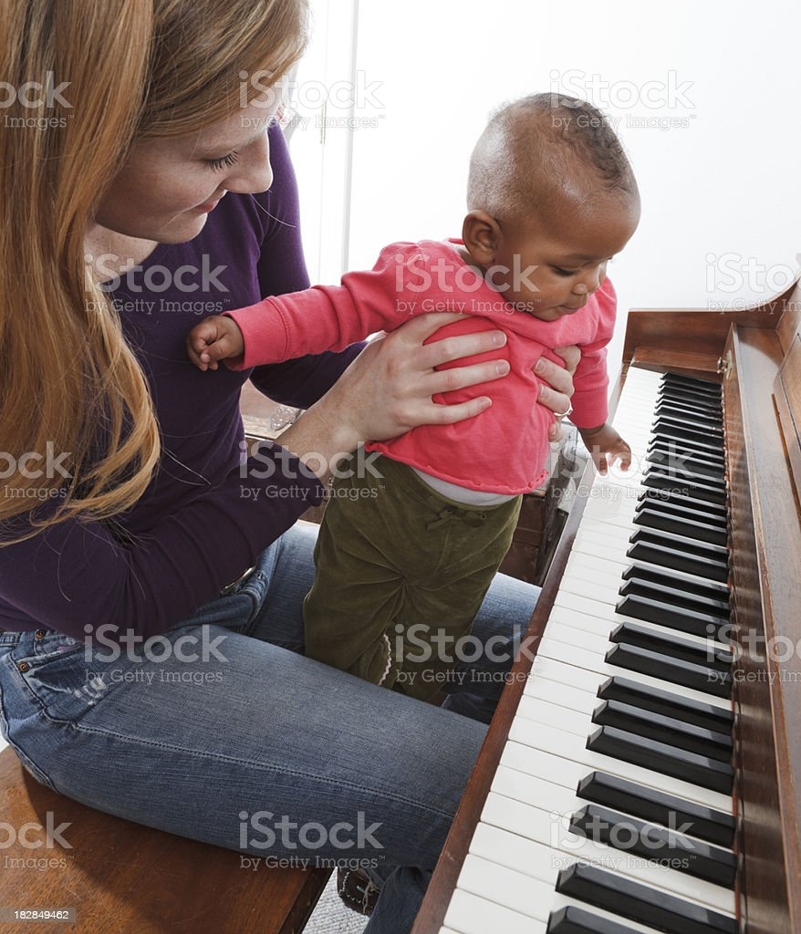 mother, adopted baby african descent multi-ethnic daughter playing piano royalty-free stock photo