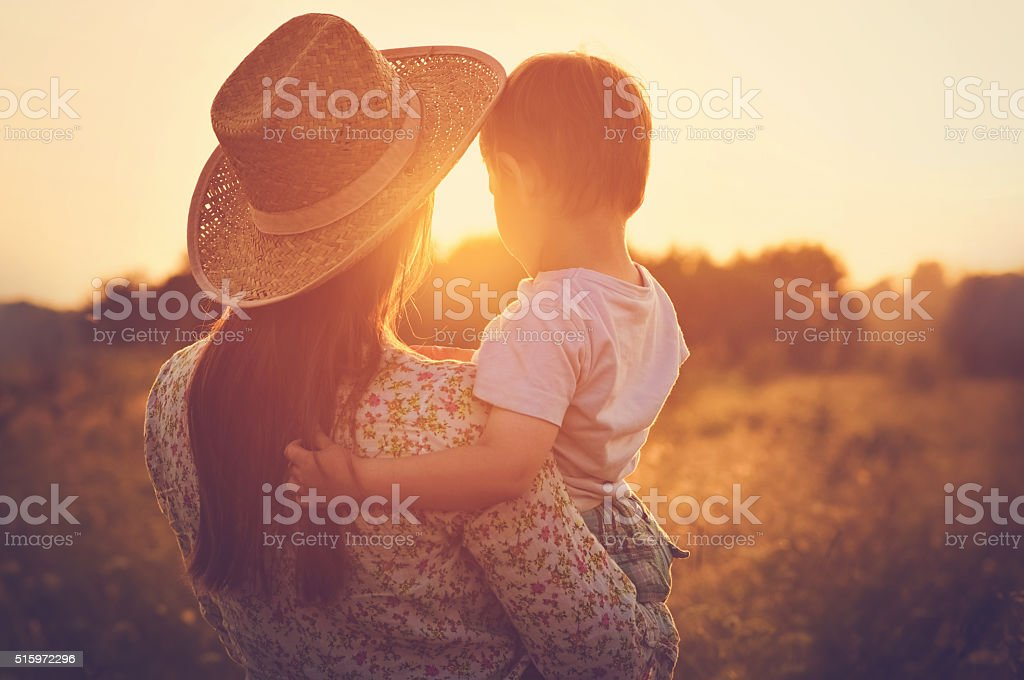 Mother and a baby enjoying beautiful sunset stock photo